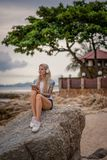 Beautiful blonde woman sitting on a rock by the sea and listening to music with your tablet. hands with tattoos. Style. Summer vacation. Modern girl stock photography