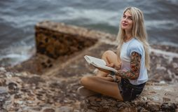 Beautiful blonde woman sitting on a stone embankment and reads book. Hands tattooed. modern, trendy, student Stock Image