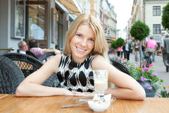 Beautiful blonde woman sitting in street cafe Royalty Free Stock Photo