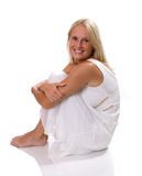 Beautiful blonde woman sitting in white dress. Beautiful blonde woman in a white dress sitting with isolated background Stock Photos