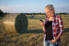 Beautiful blonde woman with smart phone in field with haystacks Royalty Free Stock Photography