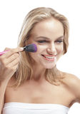 Beautiful blonde woman smiling while  applying blush on Stock Photography