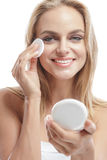 Beautiful blonde woman smiling while applying face powder Royalty Free Stock Images