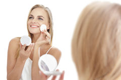 Beautiful blonde woman smiling while  applying powder Stock Image