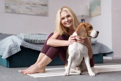 Beautiful blonde woman smiling at camera while sitting with dog. On yoga mat stock photography