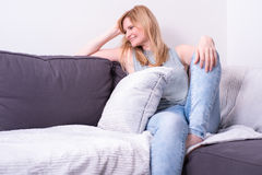 Beautiful blonde woman is smiling and relaxing on gray couch Stock Photo