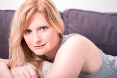 Beautiful blonde woman is smiling and relaxing on gray couch Royalty Free Stock Photo