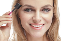 Beautiful blonde woman smiling while using eyebrows comb Royalty Free Stock Image