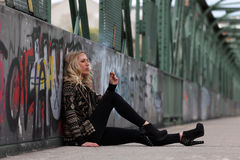 Beautiful blonde woman smoking cigarette on a bridge with graffiti Stock Photos