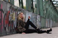 Beautiful blonde woman smoking cigarette on a bridge with graffiti Royalty Free Stock Photography