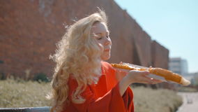 Beautiful Blonde Woman is Snacking in the Park with Appetizing Huge Sandwich stock footage