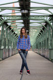 Beautiful blonde woman standing on a bridge with graffiti. Girl with long legs in blue jeans and sneakers standing on a bridge Stock Photo