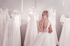 Beautiful blonde woman standing in front of wedding dresses. Difficult choice. Beautiful blonde woman standing in front of wedding dresses while thinking about stock images