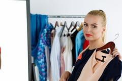 Beautiful blonde woman standing near wardrobe rack full of cloth Royalty Free Stock Image