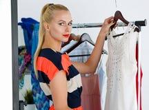 Beautiful blonde woman standing near wardrobe rack full of cloth Royalty Free Stock Photography