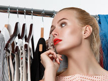 Beautiful blonde woman standing near wardrobe rack. Full of clothes and choosing dress.  Shopping and consumerism or stylist concept. Nothing to wear and hard Stock Image