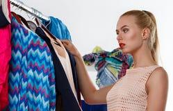 Beautiful blonde woman standing near wardrobe rack Royalty Free Stock Images