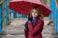 Beautiful blonde woman stands on bridge under umbrella Stock Images