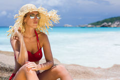 Beautiful blonde woman with straw sunhat and sunglasses, tropical environment Stock Photos