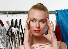 Beautiful blonde woman suffering near wardrobe rack Royalty Free Stock Photo