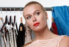 Beautiful blonde woman suffering near wardrobe rack Royalty Free Stock Image