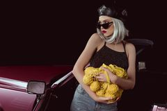 Beautiful blonde woman in sunglasses and beret holding string bag with lemons and looking away while standing. Near car stock images