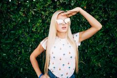 Beautiful blonde woman with sunglasses looking aside on summer vocation standing on leaves wall background. Beautiful blonde woman with sunglasses on summer Royalty Free Stock Images
