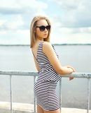 Beautiful blonde woman in sunglasses and striped dress Royalty Free Stock Photography