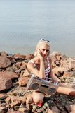 Beautiful blonde woman in swimsuit posing with vintage boombox. On rocky beach royalty free stock images