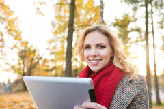 Beautiful blonde woman with tablet in colorful autumn park. Beautiful young blonde woman in red knitted scarf and checked coat holding tablet, smiling. Sunny Stock Photo
