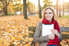 Beautiful blonde woman with tablet in colorful autumn park. Beautiful young blonde woman in red knitted scarf and checked coat sitting on wooden bench, holding Stock Photos
