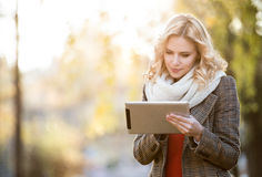 Beautiful blonde woman with tablet in colorful autumn park. Beautiful young blonde woman in white knitted scarf and checked coat holding tablet, writing. Sunny Royalty Free Stock Image