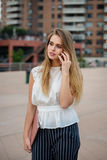 Beautiful blonde woman talking on the cell phone, holding laptop and walking on city street wearing business outfit. Stock Photos