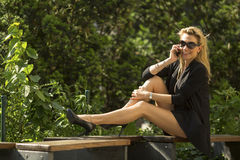 Beautiful blonde woman talking on the cell phone sitting on the bench. Royalty Free Stock Images