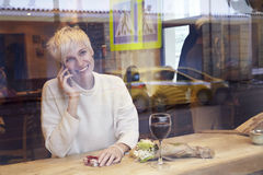 Beautiful blonde woman talking by mobile phone in cafe. Romantic breakfast for a date or St. Valentine`s Day. Present box and rose Royalty Free Stock Images