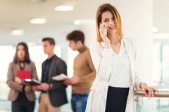 Beautiful blonde woman talking on phone. Beautiful blonde women talking on phone. Colleagues talking in the background Royalty Free Stock Photos