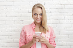 Beautiful blonde woman texting on mobilephone. Portrait of beautiful blonde woman texting on mobilephone with white brick wall background Royalty Free Stock Image