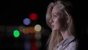 Beautiful blonde woman touch her long hair in night city. Face profile beautiful blonde woman touch her long hair in night city, slow motion stock video footage
