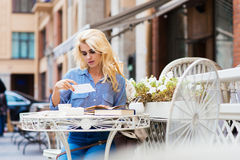 Beautiful blonde woman with trendy look sitting with books in sidewalk cafe in warm autumn day Stock Photography