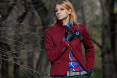 Beautiful blonde woman in tweed jacket and leather gloves in aut. Pretty woman with flowing hair in tweed jacket and leather gloves walking in autumn forest Royalty Free Stock Photos