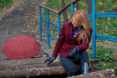 Beautiful blonde woman in tweed jacket and leather gloves sits o. Pretty woman with flowing hair in tweed jacket and leather gloves sits on the old bridge in Stock Photos