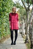 Beautiful young blonde woman in urban background. Beautiful blonde woman in urban background. Young girl wearing red dress and tights standing in the street royalty free stock images