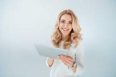 Beautiful blonde woman using digital tablet on grey. Happy beautiful blonde woman using digital tablet on grey stock image