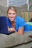 Beautiful blonde woman using laptop on couch Stock Image