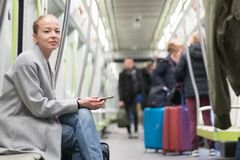 Beautiful blonde woman using smart phone while traveling by metro public transport. royalty free stock photography