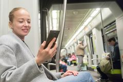 Beautiful blonde woman using smart phone while traveling by metro public transport. royalty free stock images