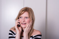 Beautiful blonde woman is very upset during a phone call Stock Image
