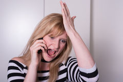 Beautiful blonde woman is very upset during a phone call Stock Photos