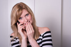 Beautiful blonde woman is very upset during a phone call Stock Photo