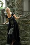 Beautiful blonde woman in vintage black dress. Sexy young blonde woman in vintage black dress or gown looking in the distance from the bottom stone staircase of Stock Image